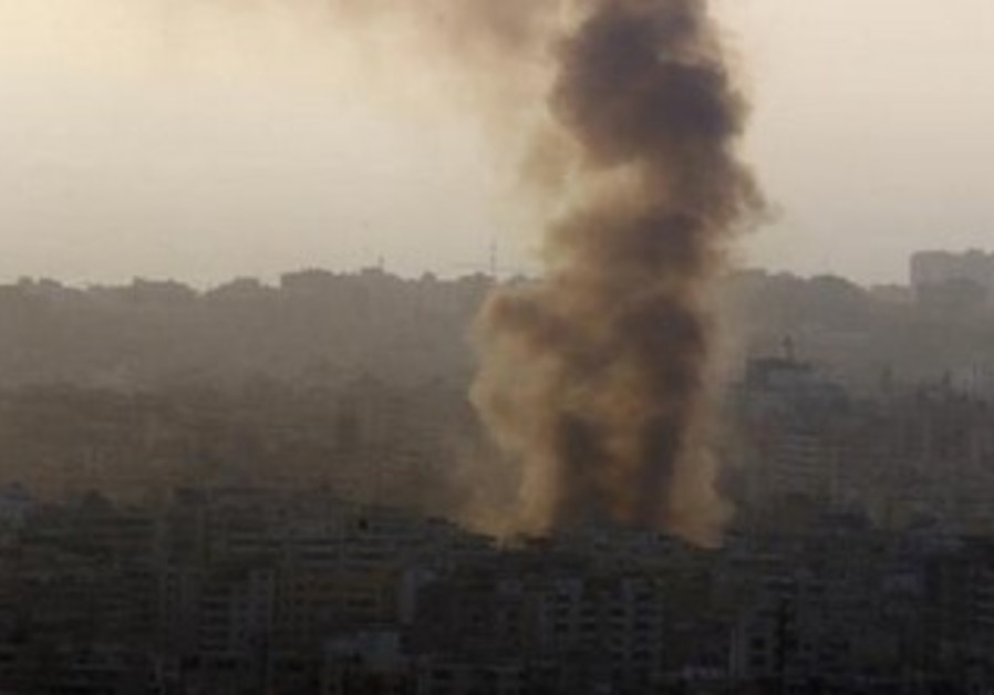 Smoke rises behind buildings from the site of an explosion in Beirut.