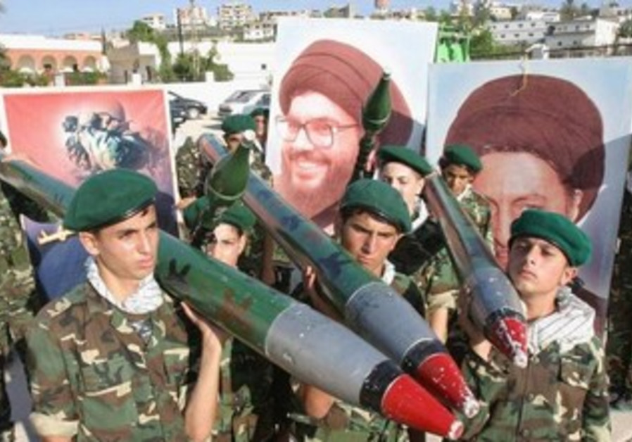 Hezbollah members carry mock rockets next to a poster of the group's leader Sayyed Hassan Nasrallah.