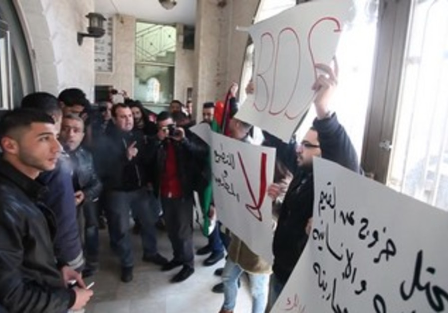 Palestinian activists protest Israeli-Palestinian activists peace meeting in Ramallah, January 9.