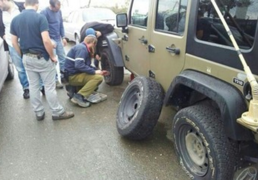 Army vehicle with punctured tires, West Bank, January 10, 2014