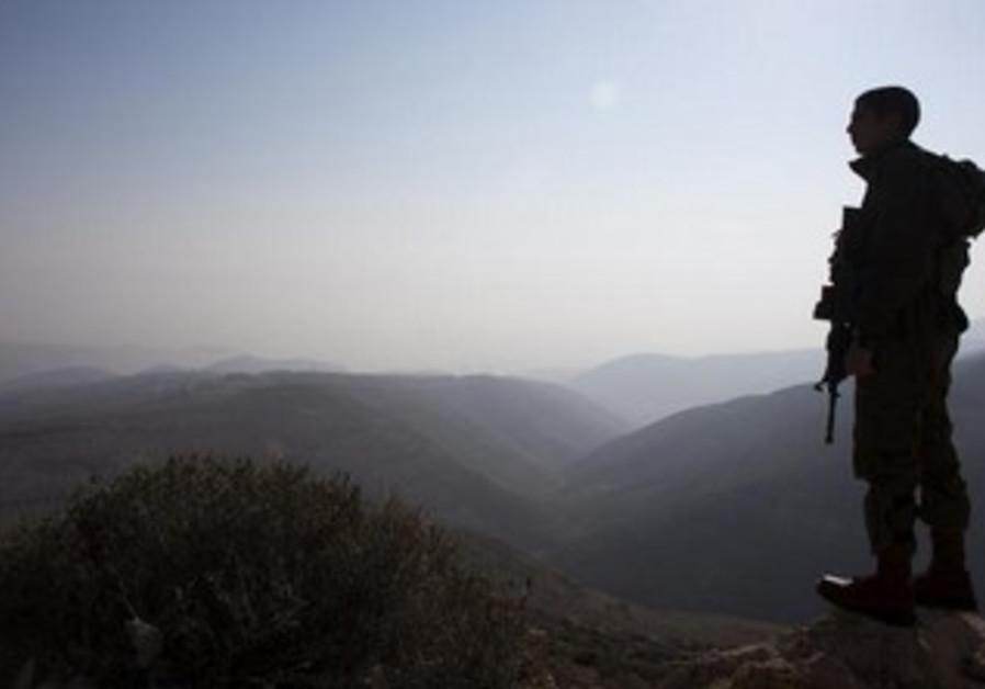 IDF soldier looking over Jordan Valley.