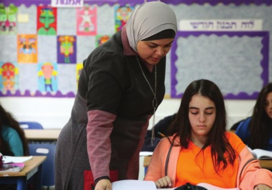 Nedaa Rabie helps a student with math at Gvanim Junior High School