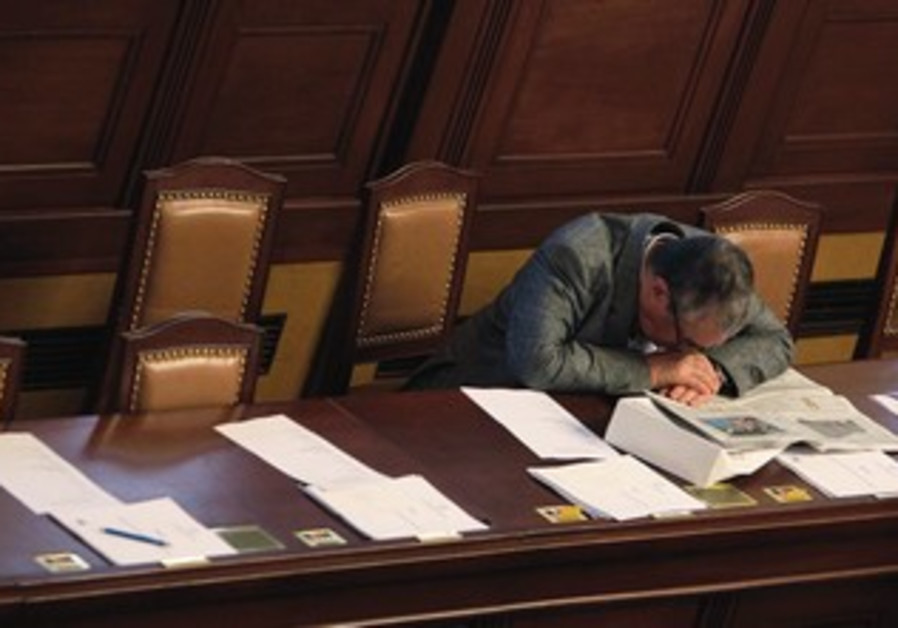 A man places his head on his desk in a fit of exhaustion.