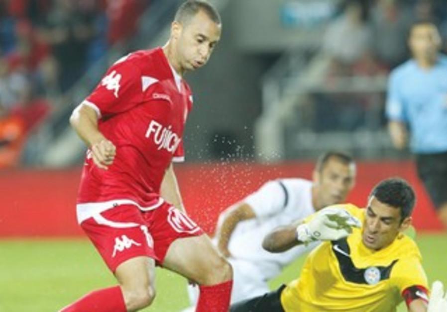 Hapoel Tel Aviv striker Omer Damari (L) beats Acre goalkeeper Dudu Goresh.