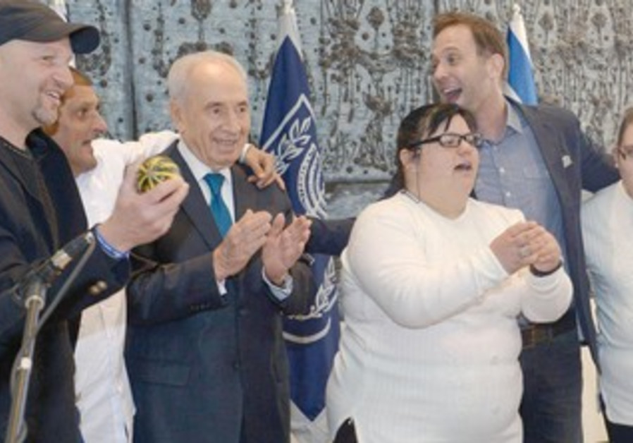PRESIDENT SHIMON PERES poses with individuals with intellectual disabilities at his residence in the