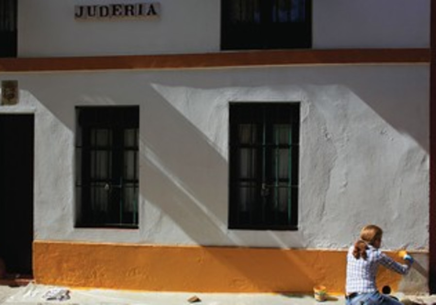 A person paints the facade of a building in the old Jewish quarter of Seville.