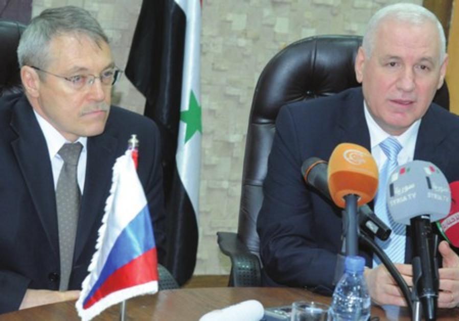 Syrian Oil Minister Suleiman al-Abbas (right) and Russian Ambassador Azmatullah Kulmohamedov