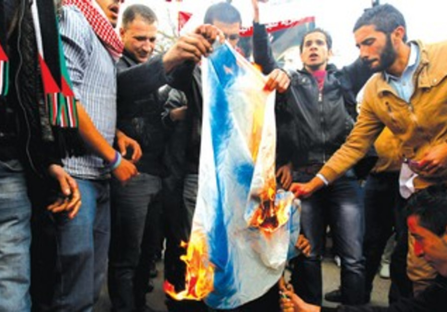 JORDANIANS BURN an Israeli flag in front of the parliament in Amman
