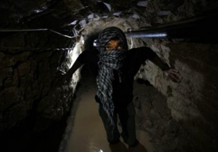Palestinian works inside a smuggling tunnel flooded by Egyptian forces