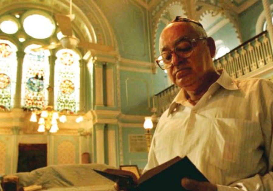 A man reads from a prayer book at a synagogue in Bombay