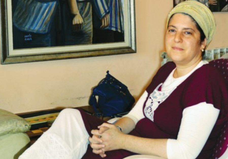 GUELA TWERSKY sits in her home