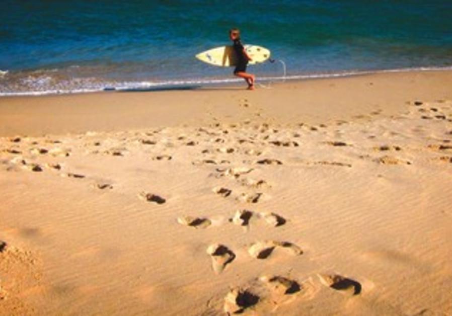 Footprints mark the sand of a beach near Melbourne