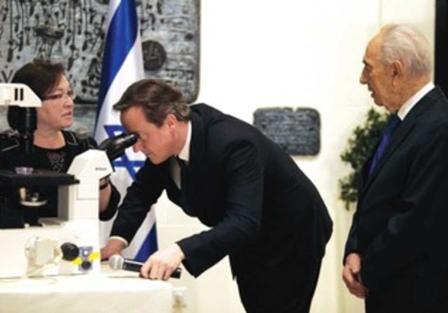 Cameron looks through a microscope at regenerating cells
