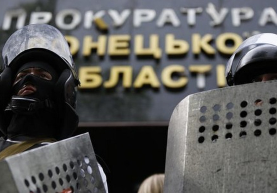 Pro-Russia activists wearing riot police helmets and shields stand guard at the entrance of the pros