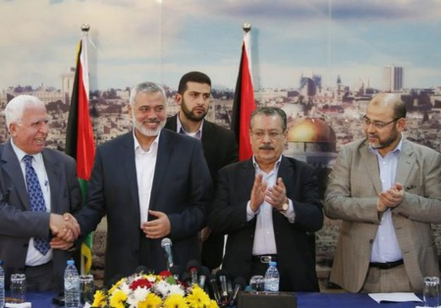 Senior Fatah official Azzam Al-Ahmed (L), shakes hands with head of the Hamas govt Ismail Haniyeh