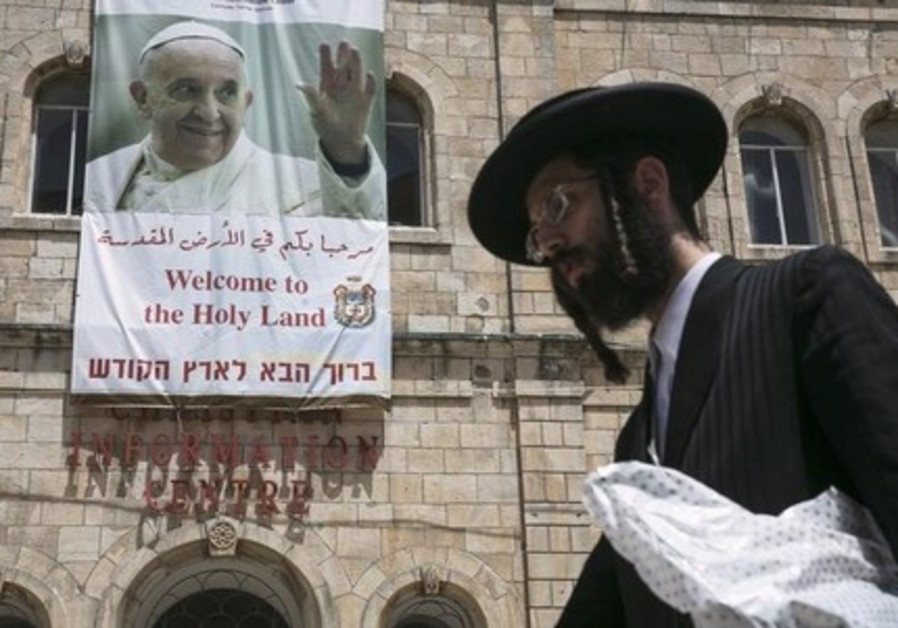 An ultra-Orthodox Jewish man walks past a banner depicting Pope Francis, in Jerusalem's Old City