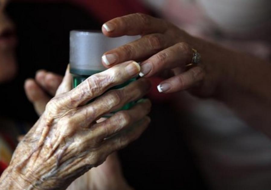 Nurse gives medication to elderly patient [Illustrative]