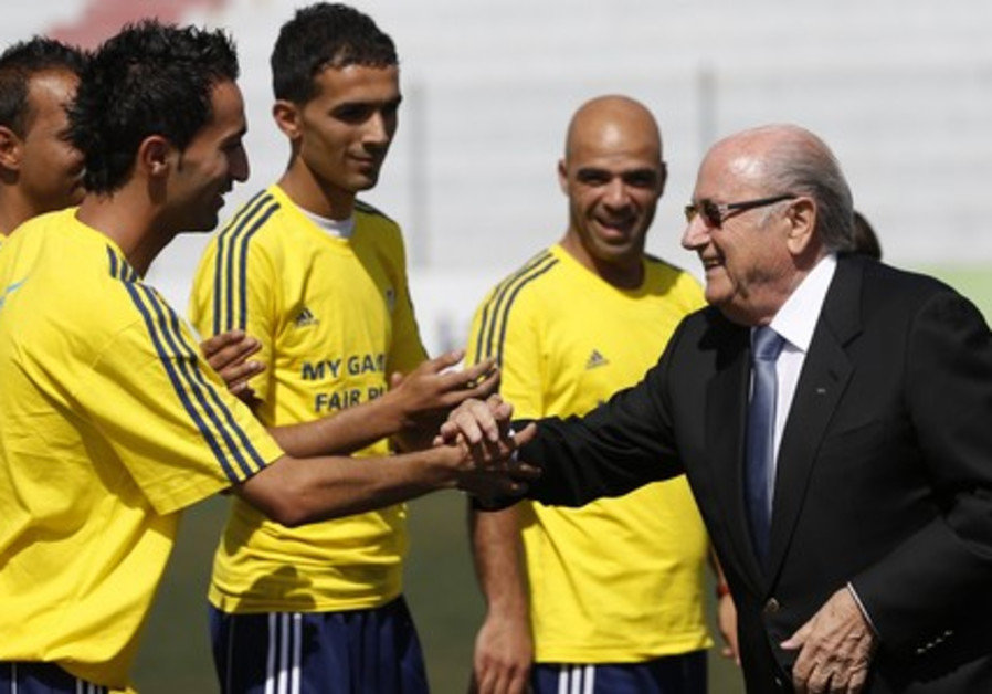 FIFA President Sepp Blatter (R) shakes hands with Palestinian coaches