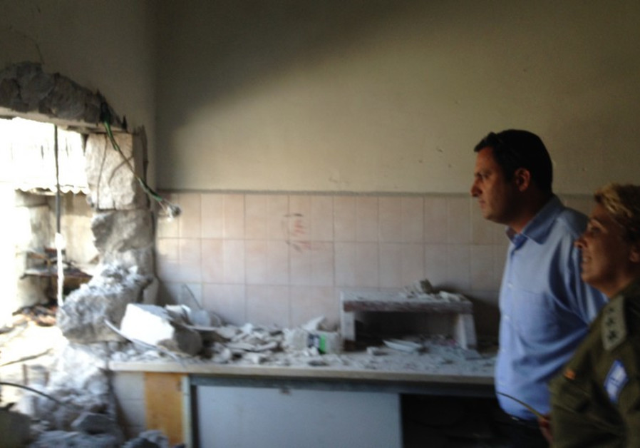 Sderot Mayor Alon Davidi with soldier in damaged building in 2014.
