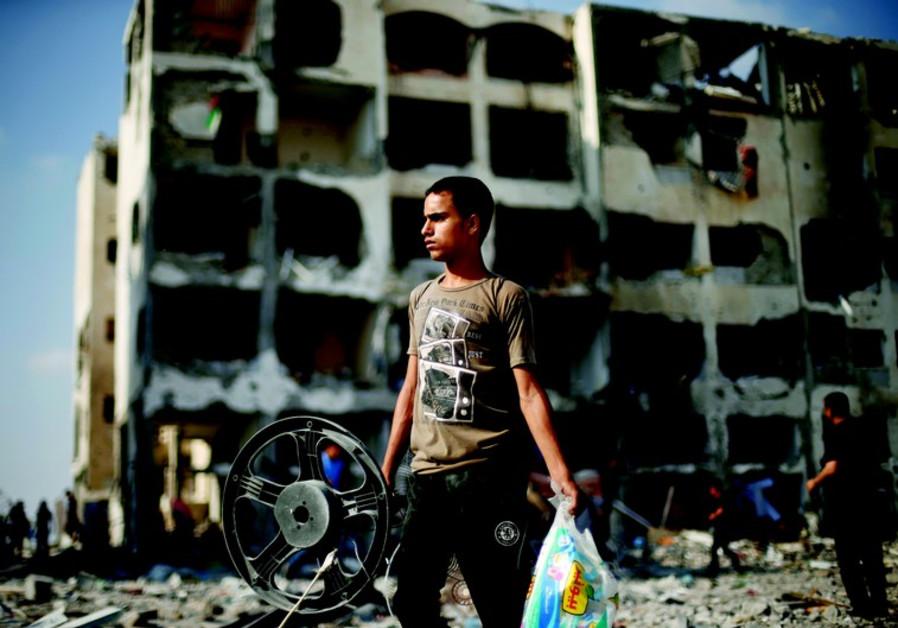 Jeune Palestinien de Beit Lahiya devant son immeuble en ruine