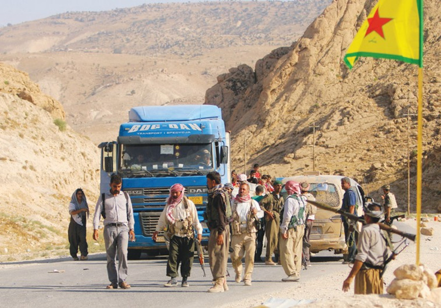 YAZIDI FIGHTERS secure a road on Mount Sinjar.