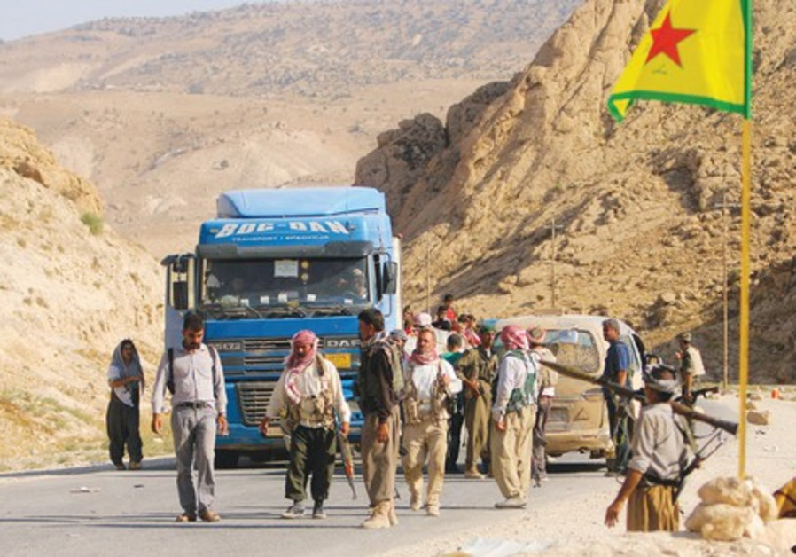 YAZIDI FIGHTERS secure a road on Mount Sinjar.