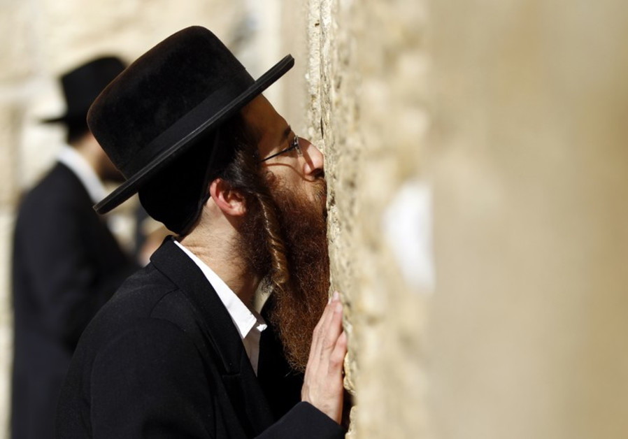 An ultra-Orthodox Jewish man kisses the Western Wall
