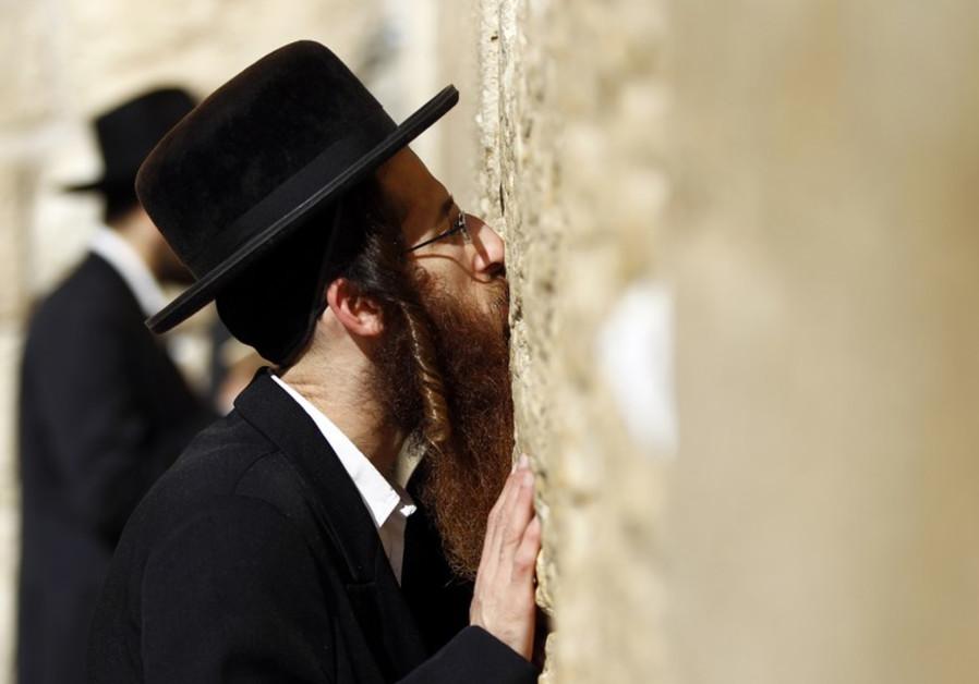An ultra-Orthodox Jewish man kisses the Western Wall
