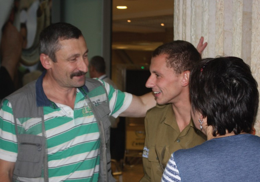 LONE SOLDIER Maksim Kolesnikov reunites yesterday at Ben-Gurion Airport with his newly arrived paren