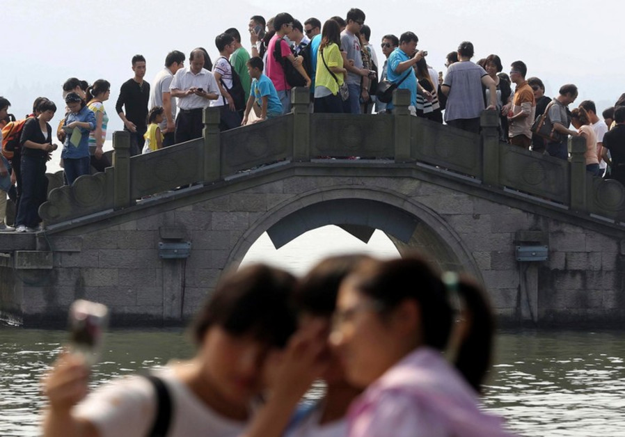 Women pose as tourists crowd bridge above West Lake, on  national holiday in Hangzhou, Zhejiang