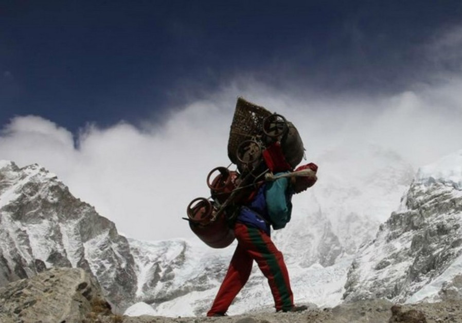 A Nepalese porter walks with his load from Everest base camp in Nepal