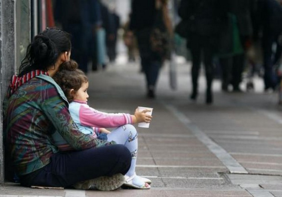 A beggar is seen with her child in central Athens