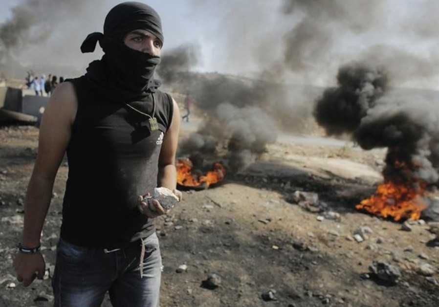 Youth holds stone as Palestinians clash with IDF in the West Bank