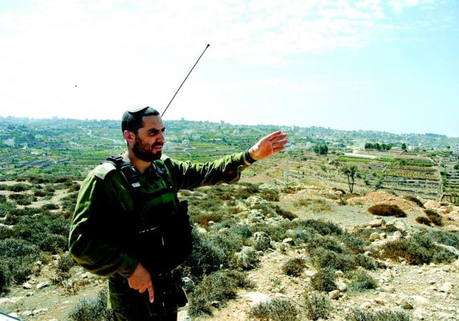 Le capitaine Eitan Dana-Picard indique un point en en surplomb sur la ville de Halhoul. Les corps de