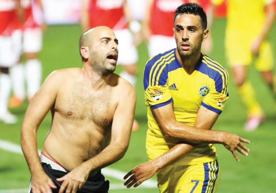 A shirtless fan takes a swing at Maccabi Tel Aviv's Eran Zahavi