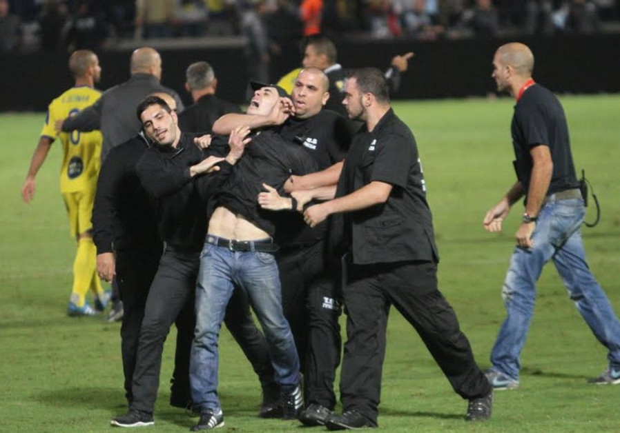Security guards haul away a fan who ran onto the pitch