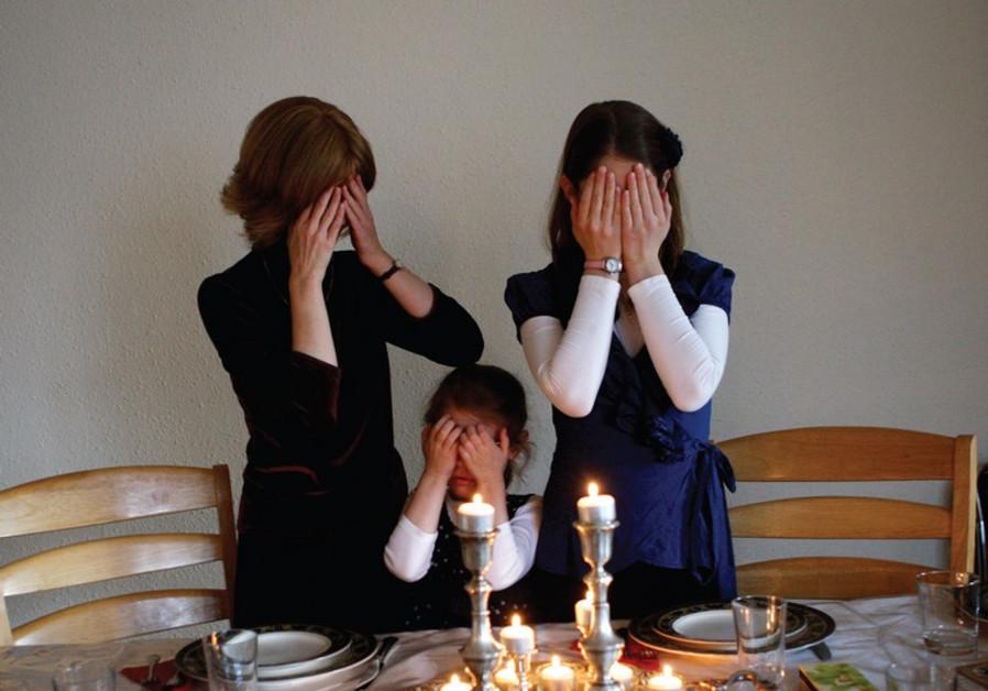 Women light candles for Shabbat