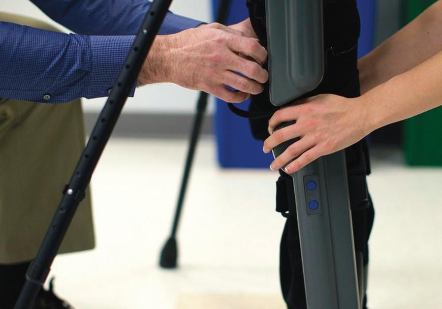 A DOCTOR and a professor of rehabilitation help a man at a school of medicine
