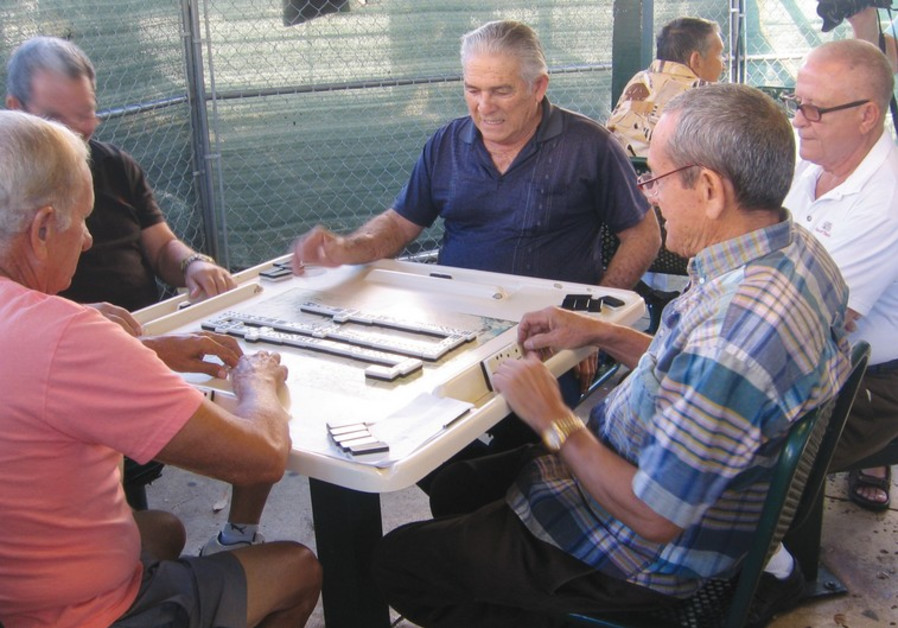 RESIDENTS OF Little Havana pass the time playing dominoes.