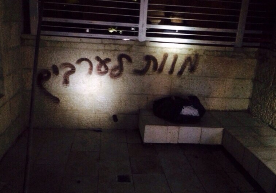 "A wall at a  bilingual Hebrew-Arabic school in Jerusalem reads ""death to Arabs."""