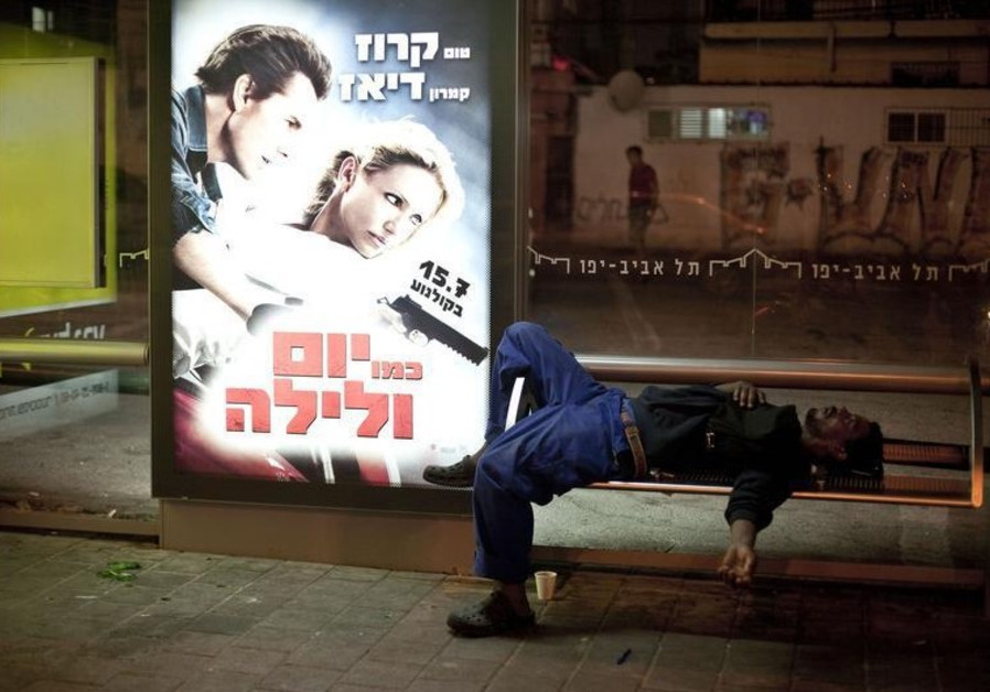 An African migrant worker sleeps on a bench of a bus station in south Tel Aviv
