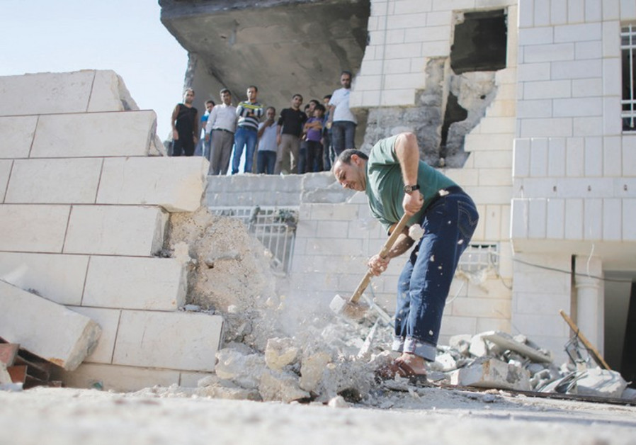 A PALESTINIAN removes a wall to allow a bulldozer access to clear the rubble