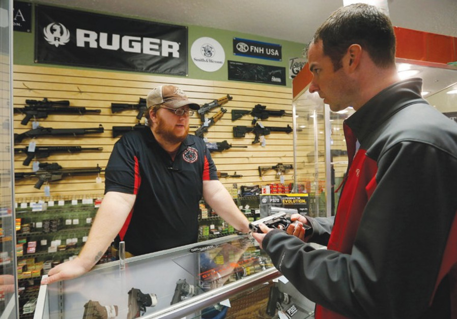 AN EMPLOYEE speaks to a customer about the purchase of a handgun at a store in Bridgeton, Missouri,