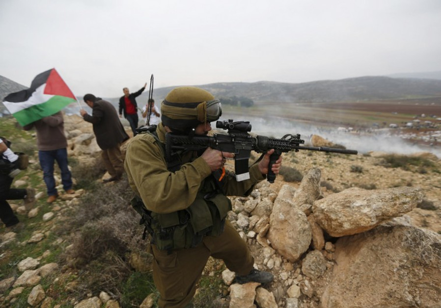 Israeli soldier aims weapon during protest near Ramallah