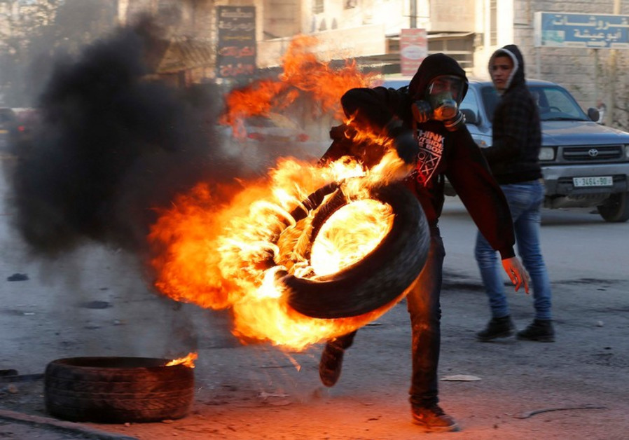 A Palestinian carries a burning tire