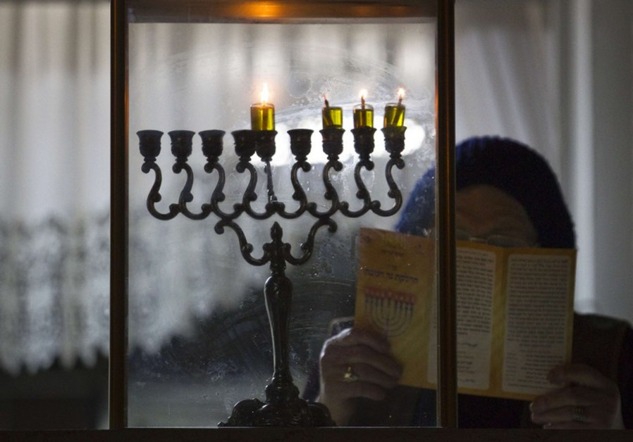 An ultra-Orthodox Jewish woman prays after lighting candles on the third night of Hanukkah