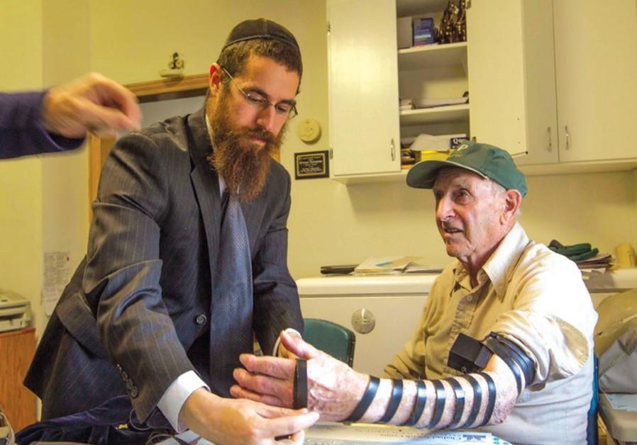 RABBI ABRAHAM SIMMONDS helps Harvey Kleiman put on tefillin.