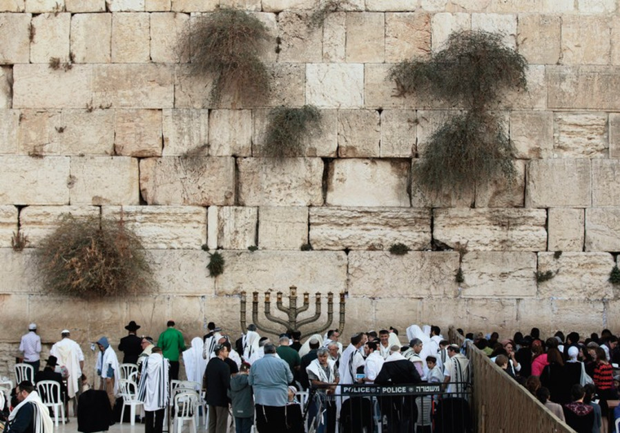 WORSHIPERS PRAY at the Western Wall in the capital during Hanukka last year.
