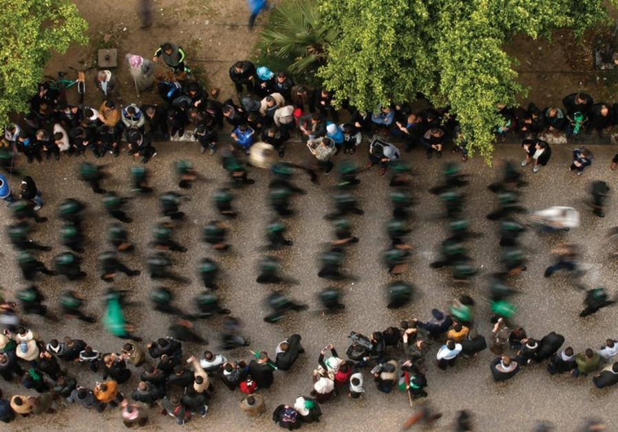 PEOPLE WATCH as Palestinian members of al-Qassam Brigades parade in Gaza