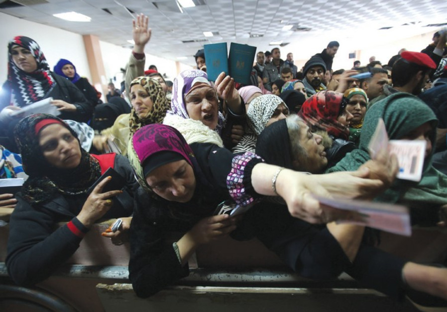 WOMEN PRESENT their passports as they ask for permits to cross from Gaza into Egypt